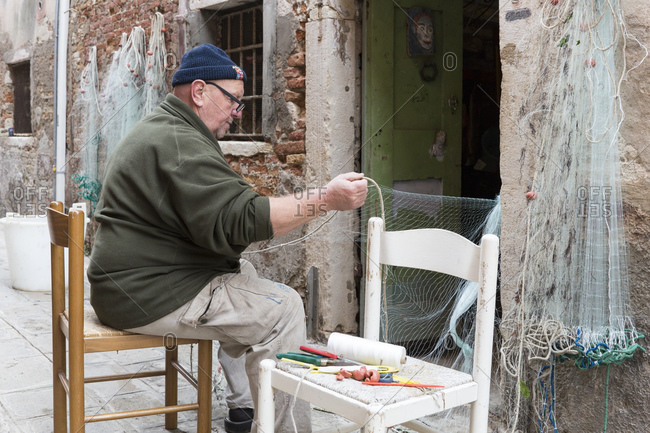 November 15, 2015: Fisherman repairing his nets in the Castello district, Venice, Italy