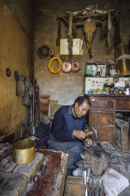 October 8, 2012: Tibetan artisan for prayer wheels at Labrang Monastery, Xiahe, China
