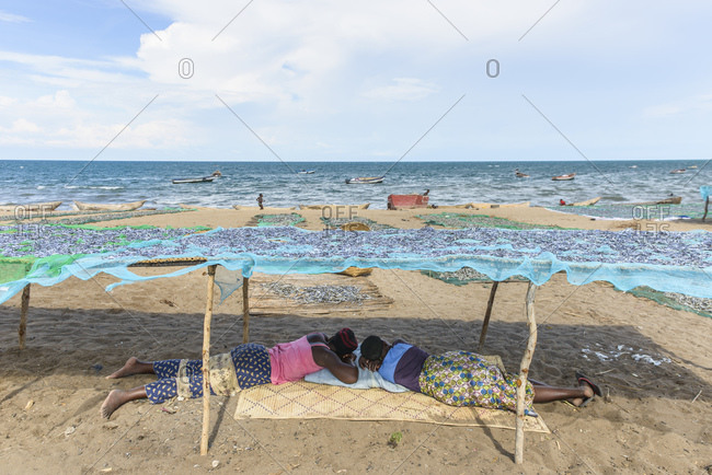 Two women are resting on a fish market on Lake Malawi, Malawi, Africa