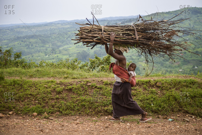 October 20, 2014: Woman with baby carries tree branches on her head, Uganda, Africa