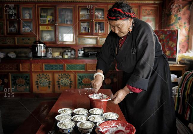 September 11, 2011: A Tibetan woman prepares bowls of yak yoghurt for the lamas, Tibetan plateau