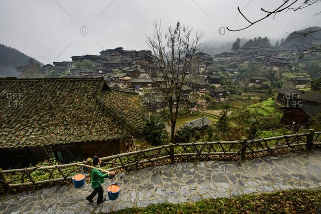 Miao woman carries food waste in XiJiang, traditional village of the Miao ethnic minority. Guizhou Province, China