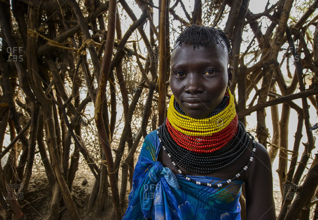 August 1, 2014: Turkana women wear their traditional necklaces, inside their hut made of branches and leaves. Kenya
