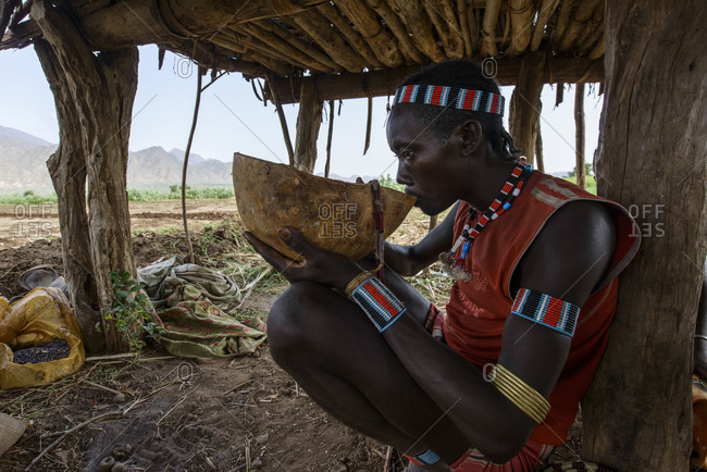 July 28, 2014: Man of Hamar tribe in Omo Valley is taking a break and drinking home-made wine, Weyto, Ethiopia
