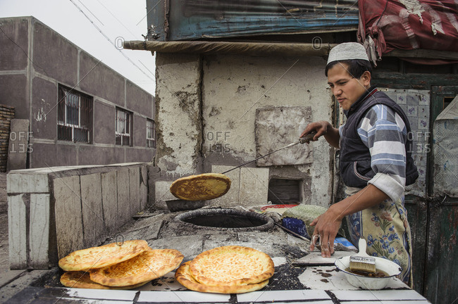 May 16, 2010: The streets of Urumqi capital of Xinjiang are filled with Uighur men baking bread on the street.