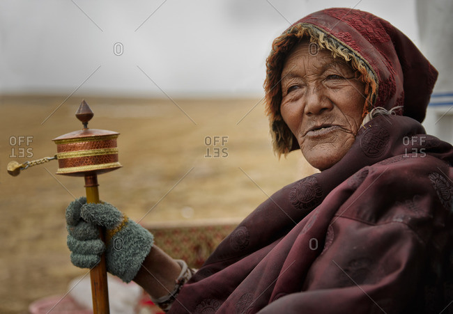 October 3, 2011: Tibetans are very devote buddhists and at all ages they spend long hours reciting their mantras using their praying wheels. Remote Tibetan plateau