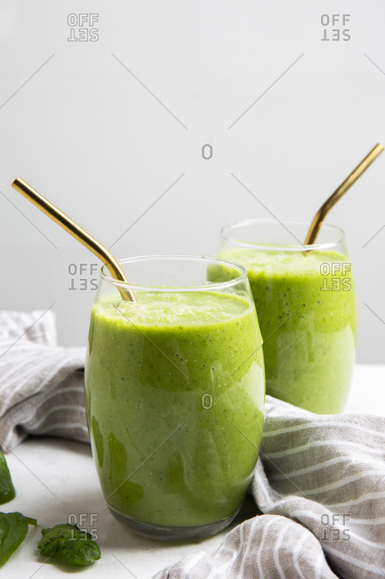 Two Green Smoothies served in a glass with a straw on a marble table top