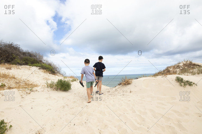 Two boys climbing up a sandy hill by the ocean under cloudy sky
