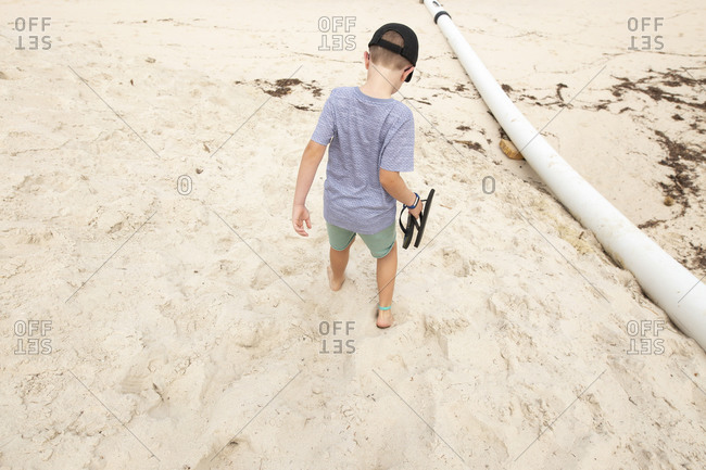 Boy carrying flip flops while walking barefoot on a sandy beach