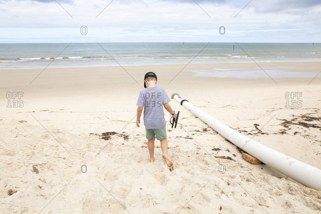 Boy carrying flip flops while walking barefoot on a sandy beach by the ocean