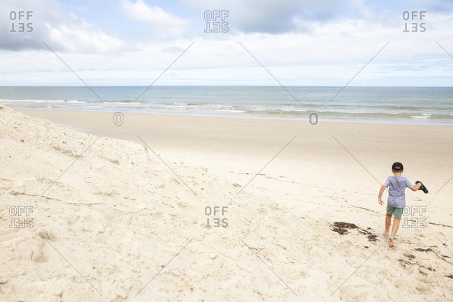 Rear view of boy carrying flip flops while walking barefoot on a sandy beach by the ocean