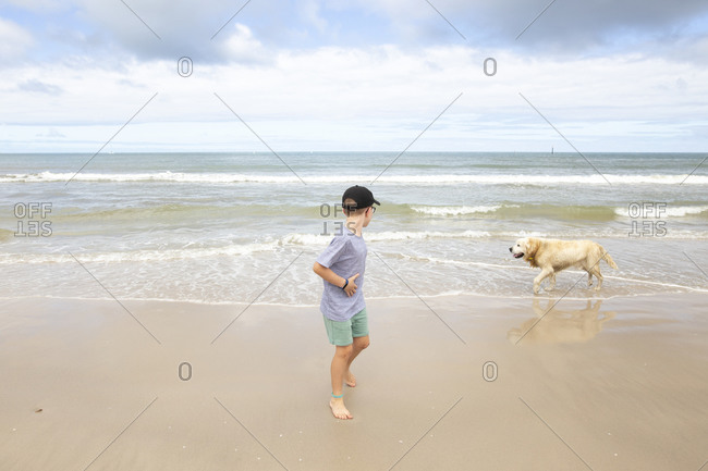 Boy running from dog while playing in the ocean waves