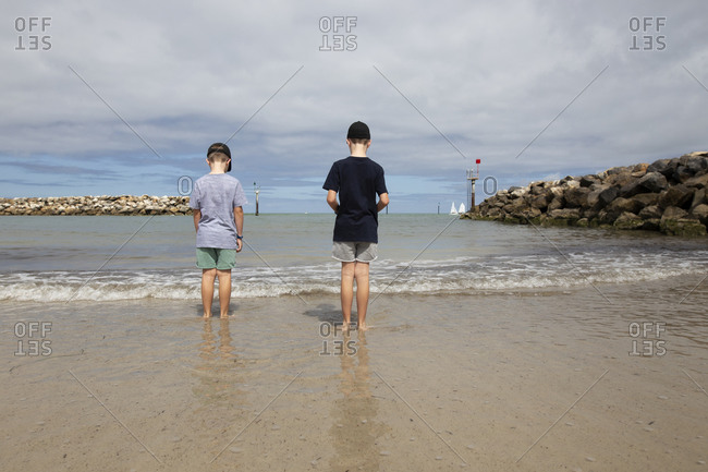 Two boys looking out at boats in the harbor under cloudy skies
