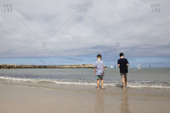 Two boys putting feet in the waves at the harbor under cloudy skies