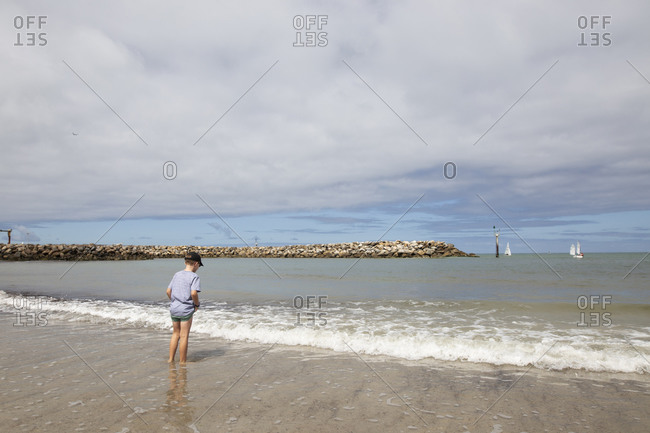 Rear view of boy dipping his feet in the ocean tide