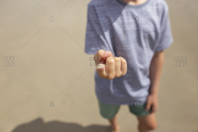 Childing holding a tiny seashell on the tip of his finger