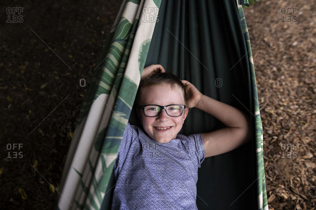 Young happy boy relaxing in a hammock