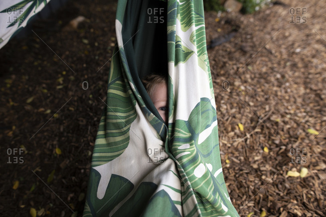 Child peeking out from a hammock