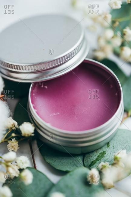 Purple handmade lip balm in a metal tin