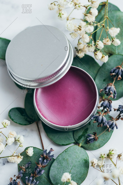 Overhead view purple handmade lip balm in a metal tin