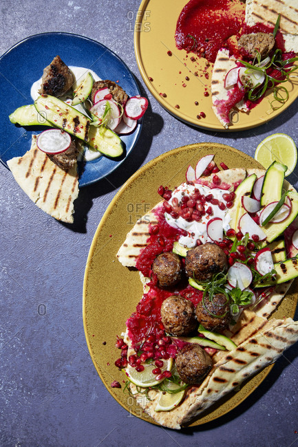 Overhead view of meatballs, beetroot hummus and pita bread being served