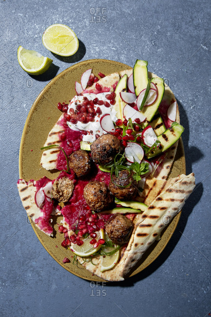 Meatballs, beetroot hummus and pita bread viewed from above