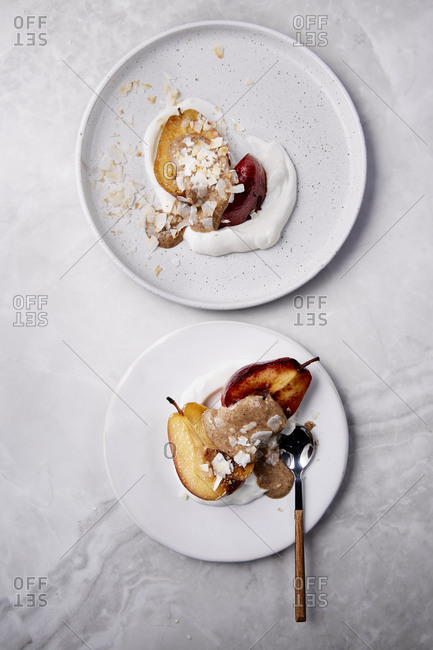 Two plates with poached pears on yoghurt with nut butter and coconut flakes