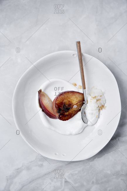 Poached pears with yoghurt and nut butter with coconut flakes