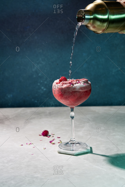 Pink cocktail garnished with raspberries and sorbet and a mixer pouring the drink into glass