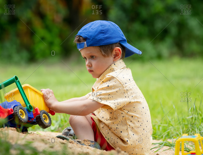 Little toddler boy playing with plastic dump truck in an outdoor sandbox