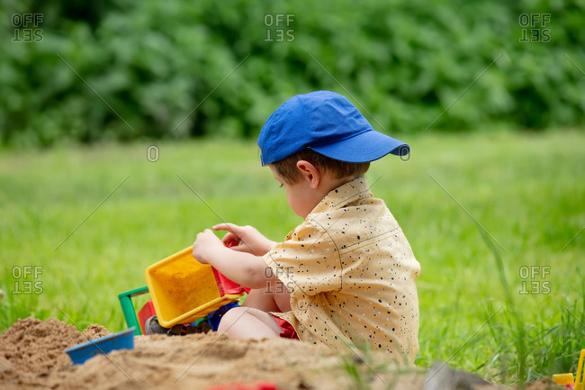 Toddler boy playing with plastic dump truck in an outdoor sandbox