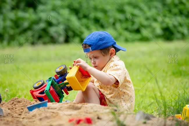 Little toddler boy concentrating while playing with plastic dump truck in an outdoor sandbox