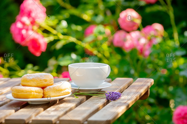 Coffee and donuts on a wooden table in a garden with roses in background