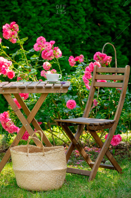 Cup of coffee and lavender flower on a table with roses on background