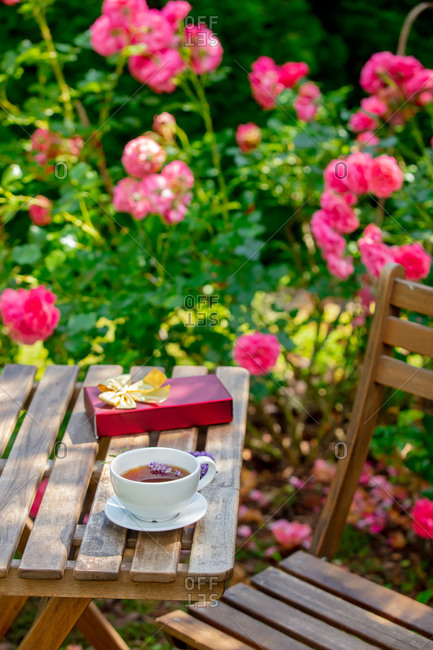 Cup of coffee and gift box on a wooden table in a garden with roses in the background
