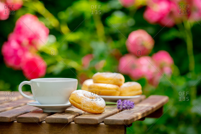 A cup of coffee and donuts on a wooden table in a garden with roses in background