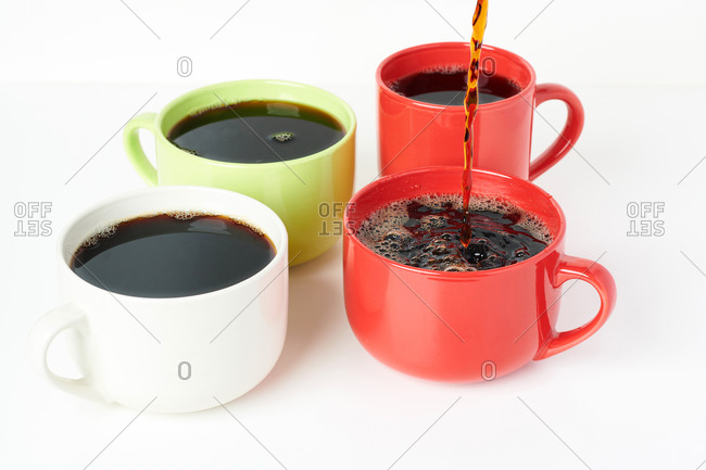 Four coffee mugs with coffee being poured into a red one