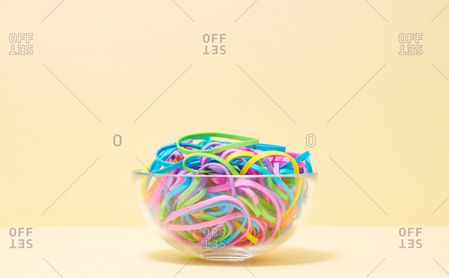 Various colored rubber bands in a bowl