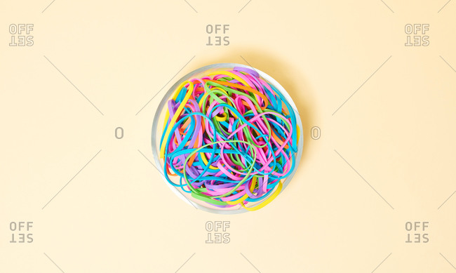 Overhead view of various colored rubber bands in a bowl