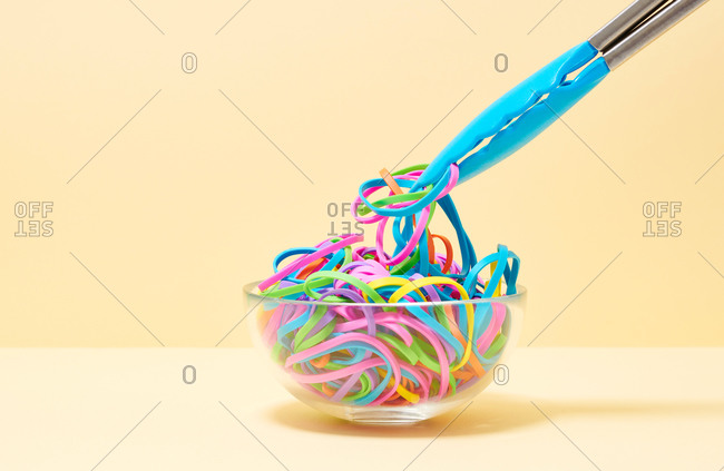 Tongs picking up various colored rubber bands in a bowl