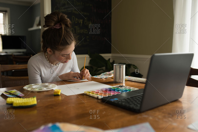 Tween girl concentrating while painting watercolor art for remote learning