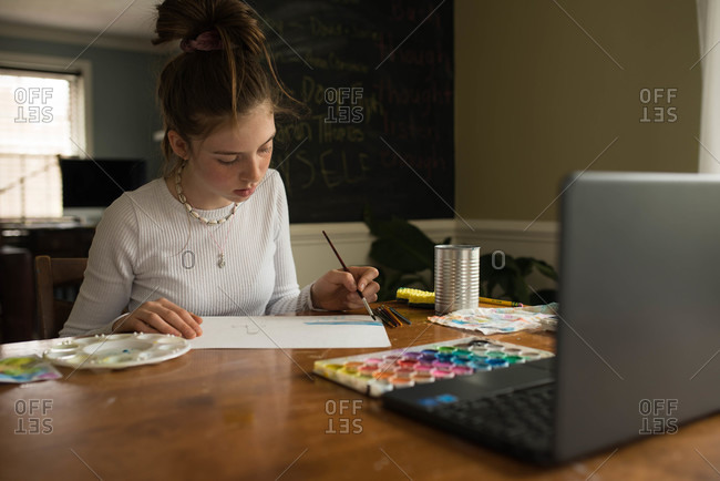 Tween girl painting with watercolors while using computer for remote learning