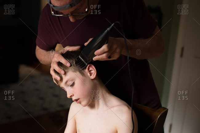 Father cutting son's hair with clippers at home