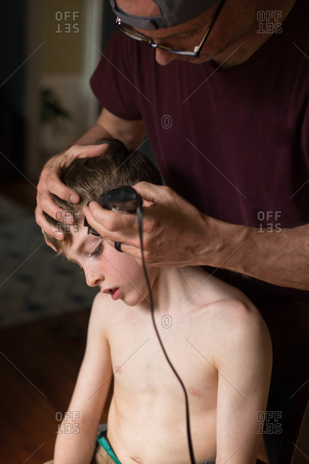 Man cutting his son's hair with clippers at home