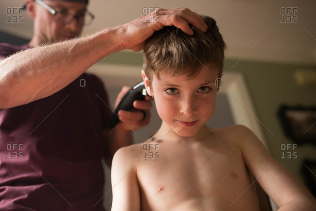Boy gets a haircut from his father at home