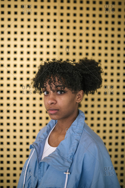 Portrait of young black woman outdoors in front of a yellow background turning to face camera