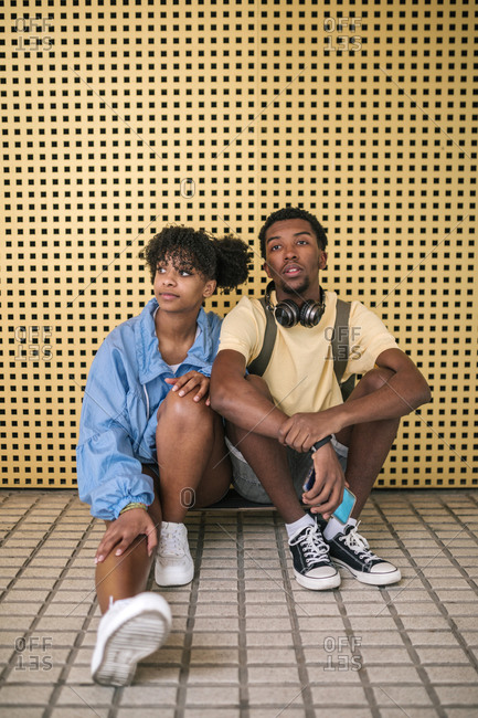 Couple of black teenagers sitting on a skateboard with a yellow background