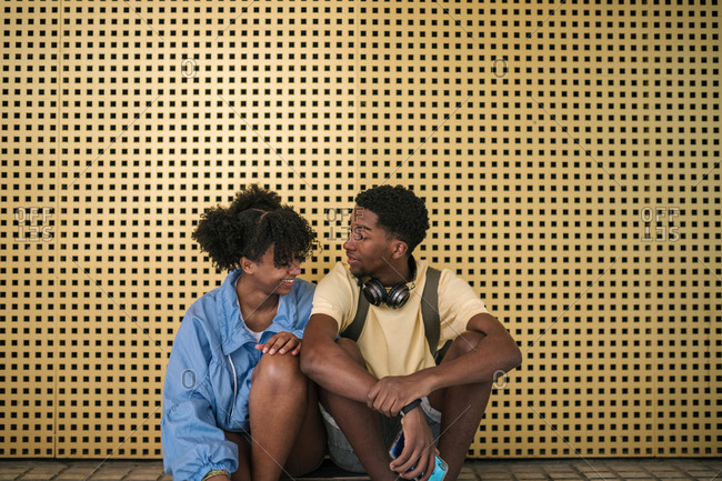 Couple of black teens sitting on a skateboard with a yellow background