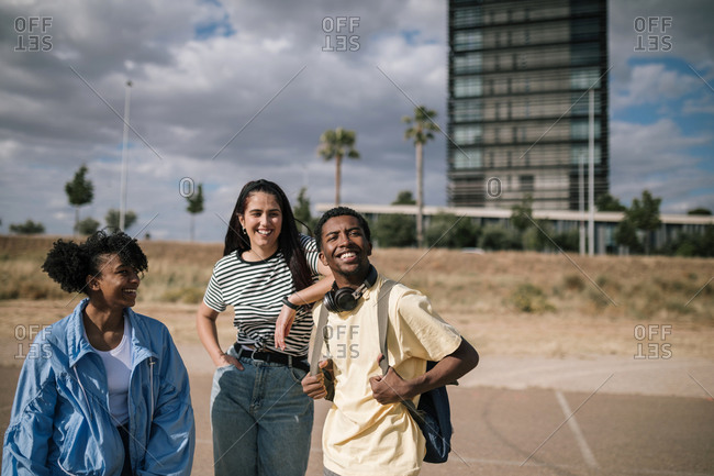 Group of three multiracial friends together in the city