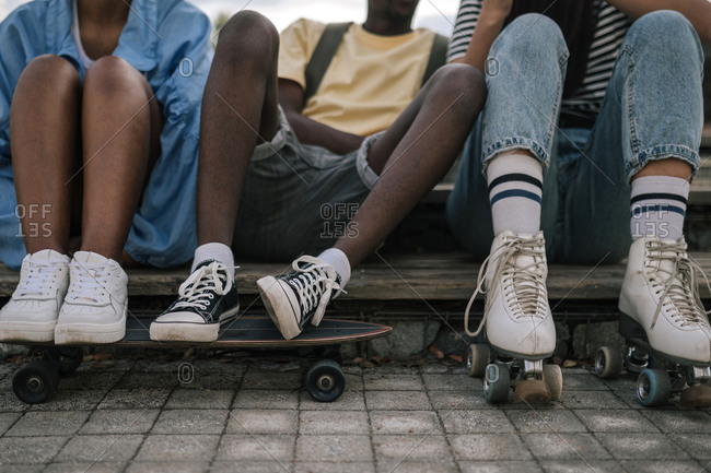 Group of multiracial teens resting while skateboarding through the city
